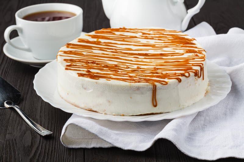 Torta de miel hecha en casa con crema agria en una tabla de madera con las pasas y las nueces fotografía de archivo