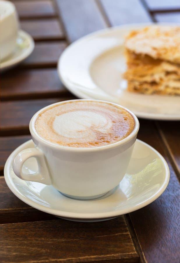 Torta de Napoleon, café del capuchino en una tabla de madera en el mirador en el café, en el jardín foto de archivo