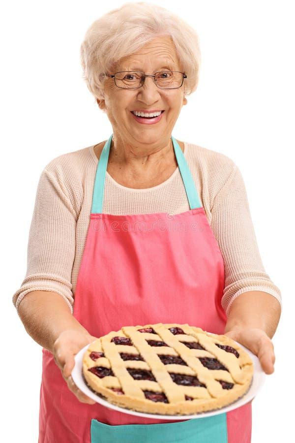 Torta de oferecimento da mulher idosa imagens de stock
