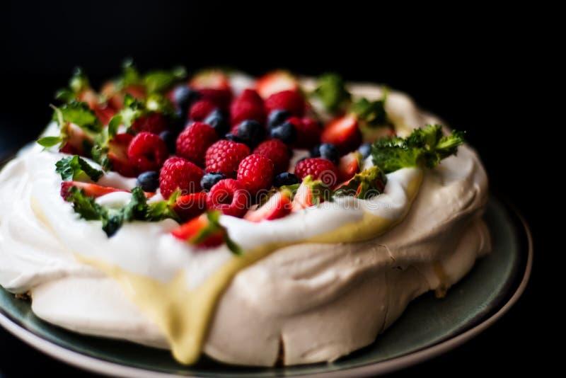 Torta de Pavlova con crema y bayas del tonka fotos de archivo