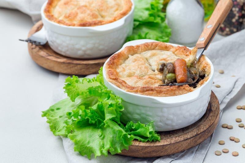 Torta de potenciômetro do vegetariano com a lentilha, o cogumelo, a batata, a cenoura e as ervilhas verdes, cobertos com a massa  imagens de stock