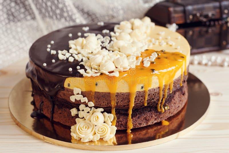 Torta de Romaantic con el esmalte del chocolate, las flores poner crema y el PA del mango fotografía de archivo libre de regalías