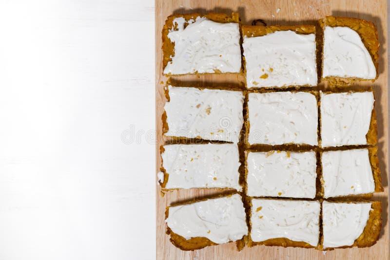 Torta de zanahoria con la formación de hielo en el tablero de madera, visión superior imagenes de archivo