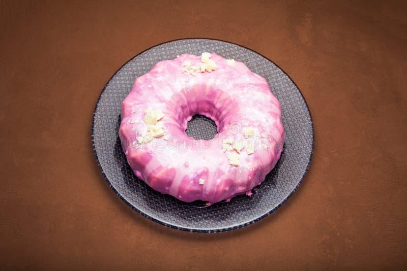 Torta de zanahoria con la formación de hielo rosada, el chocolate blanco y la plata comestible como ornamento Una torta rosada imagen de archivo