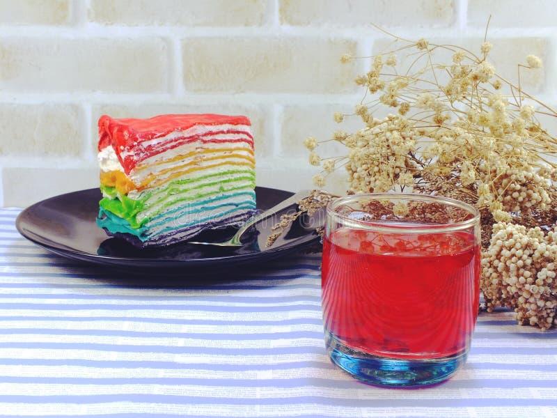 Torta del arco iris y zumo de fruta coloridos imagen de archivo libre de regalías