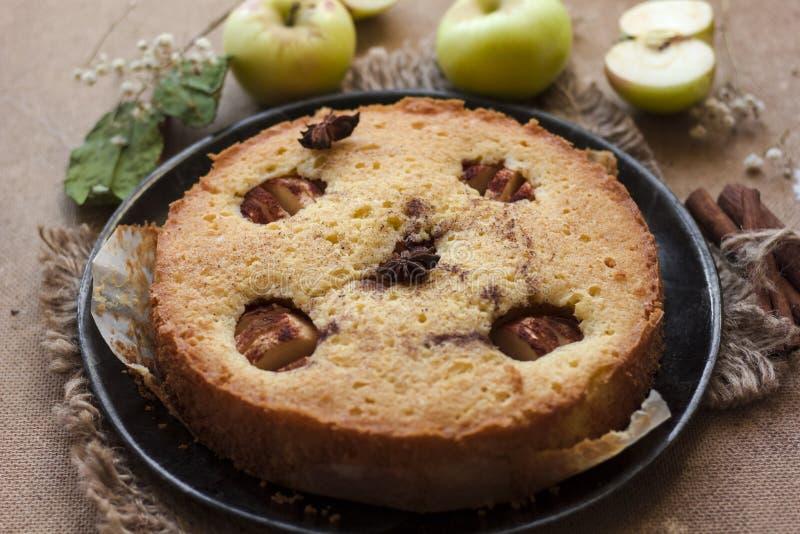 Torta del canela de Apple, palillos de canela, manzanas en la tabla fotografía de archivo