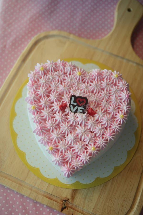 Torta del corazón de la vainilla con crema rosada de la mantequilla en la placa de madera imágenes de archivo libres de regalías
