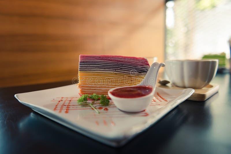 Torta del crepé del arco iris y salsa de la fresa en la placa blanca con una taza de café caliente en la tabla de madera oscura imagenes de archivo