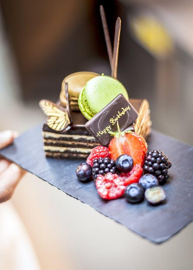 Torta del feliz cumpleaños con las frutas frescas y los macarrones imagen de archivo