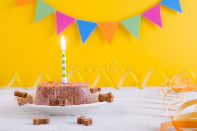 Torta del feliz cumpleaños para el perro de la comida y de las invitaciones mojadas con la vela en fondo amarillo del partido imagen de archivo