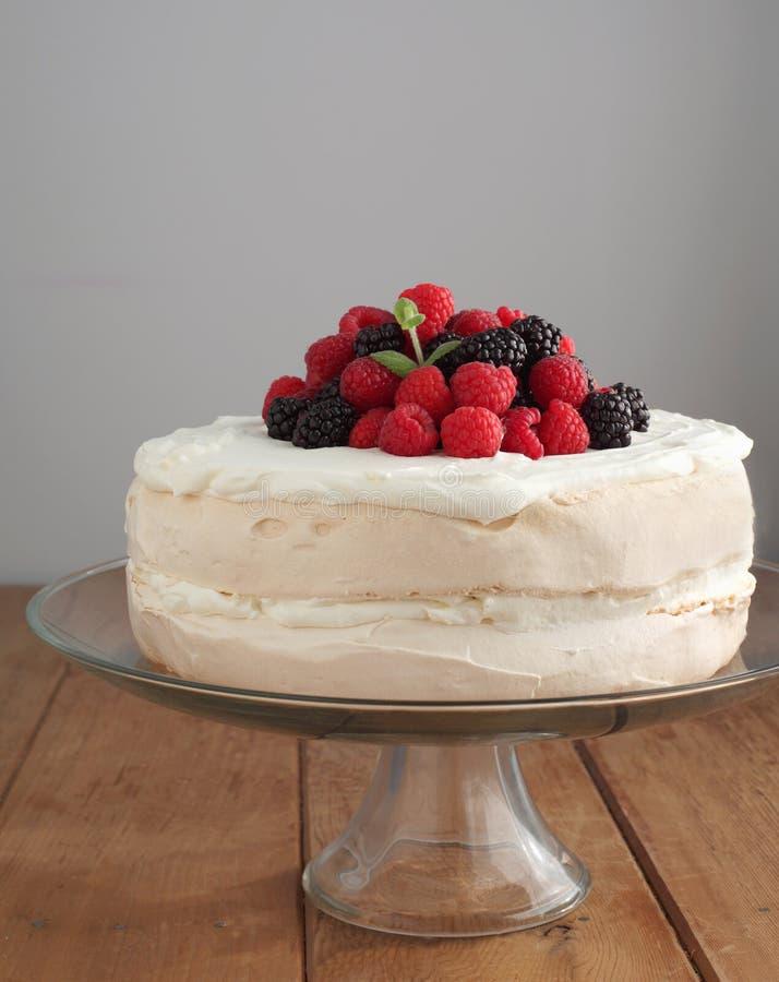 Torta del merengue con las bayas fotos de archivo