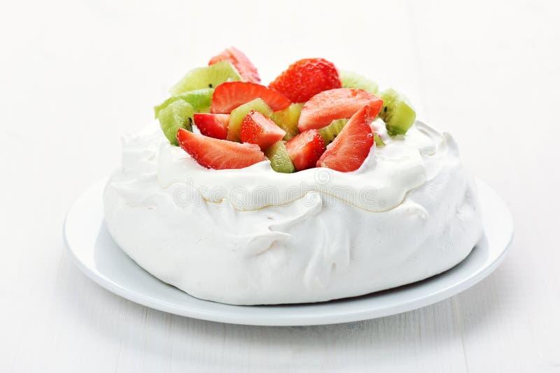 Torta del merengue con las fresas y el kiwi fotografía de archivo