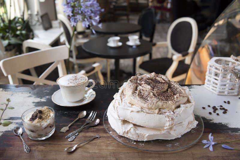 Torta del merengue, cucharas y bifurcaciones del vintage, postre y café en el fondo de un café del vintage foto de archivo