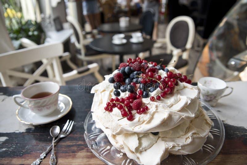 Torta del merengue, cucharas y bifurcaciones del vintage, postre y café en el fondo de un café del vintage imágenes de archivo libres de regalías