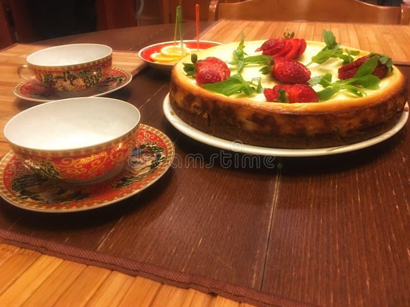 Torta del pastel de queso adornada con las hojas y las fresas de menta foto de archivo