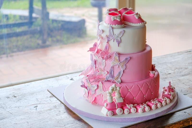 Torta del pu?o para un peque?o cumplea?os del beb? para celebrar el bautismo - dise?o rosado de la torta acodada del sugarpaste n imagen de archivo