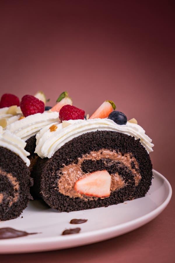 Torta del rollo del chocolate con las bayas y la crema fresca en fondo marrón imagenes de archivo