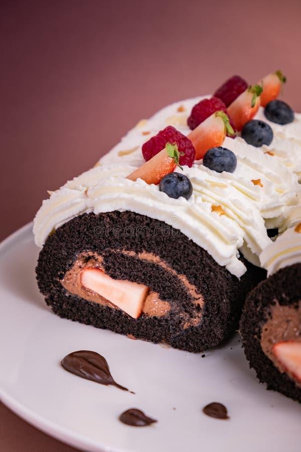 Torta del rollo del chocolate con las bayas y la crema fresca en fondo marr?n imagenes de archivo