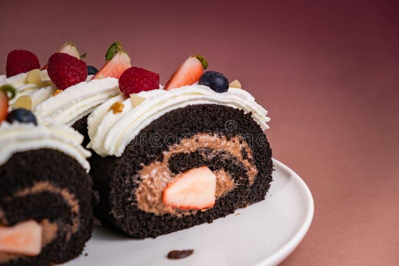 Torta del rollo del chocolate con las bayas y la crema fresca en fondo marr?n fotografía de archivo libre de regalías