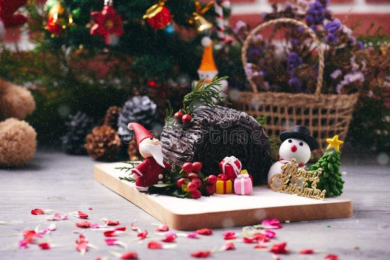 Torta del rollo del chocolate de la Navidad que coloca así como el muñeco de nieve, el azúcar de Santa Claus, el árbol de navidad foto de archivo libre de regalías