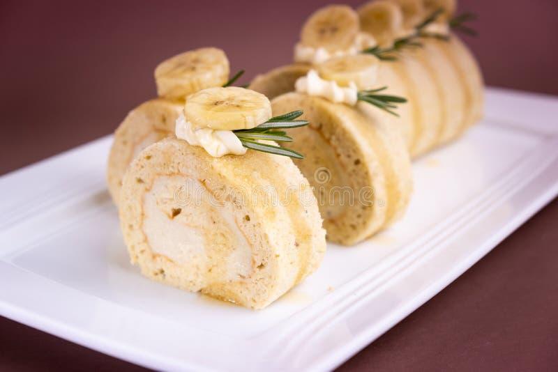 Torta del rollo del plátano con crema fresca en fondo marrón imagen de archivo
