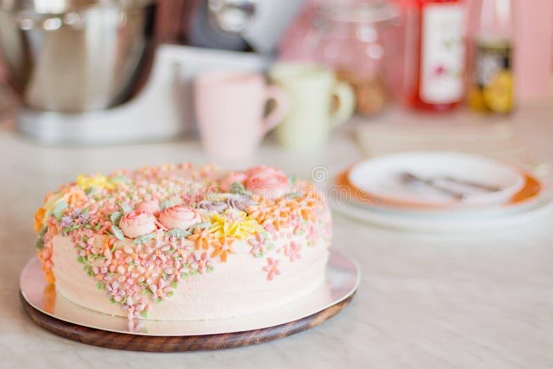 Torta del rosa en colores pastel adornada con las flores poner crema en cocina imágenes de archivo libres de regalías