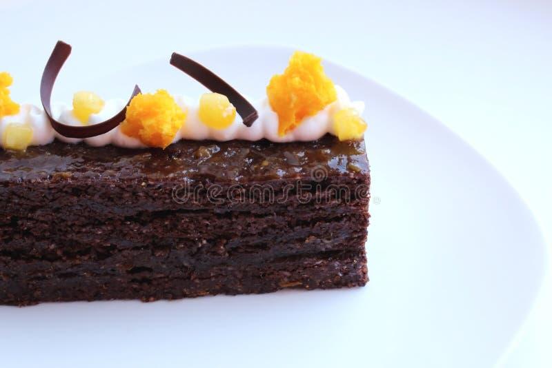 Torta del Torte de Sacher con los pedazos del albaricoque y decoración anaranjada de la esponja de la microonda en la placa blanc imagen de archivo libre de regalías