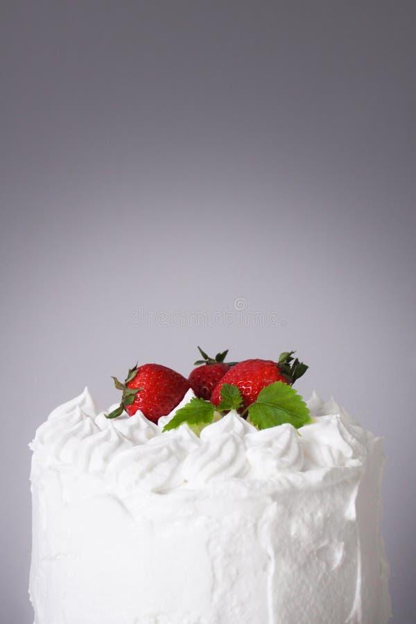 Torta deliciosa blanca grande con crema y adornada con las fresas y la menta en un soporte transparente en un fondo gris imágenes de archivo libres de regalías