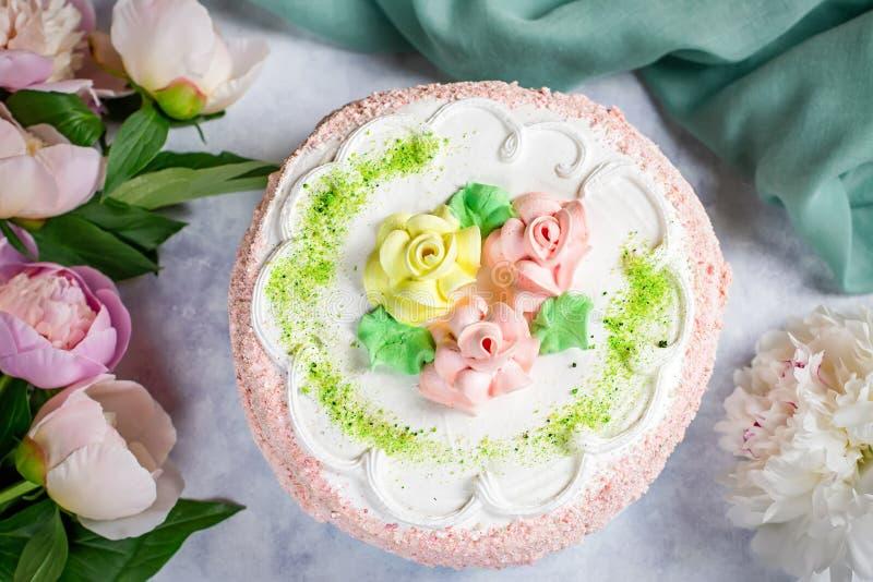 Torta deliciosa hermosa adornada con las flores en colores en colores pastel en la tabla de madera con las peonías, visión superi fotografía de archivo