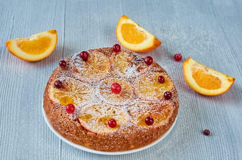 Torta dell'agrume con le arance caramellate e le bacche rosse fresche in polvere sulla superficie grigia Appena torta di appoggio fotografia stock libera da diritti