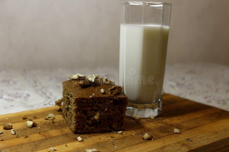 Torta della banana con un bicchiere di latte sul bordo immagini stock libere da diritti