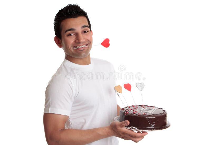 Torta di cioccolato della holding dell'uomo con i cuori di amore fotografie stock libere da diritti