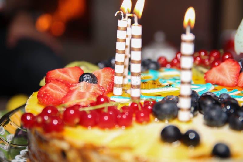 Torta di compleanno con alcune candele accese bacche immagine stock
