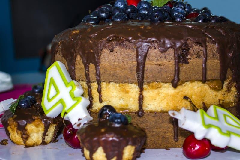 Torta di compleanno con cioccolato ed i frutti e le candele rossi di compleanno fotografie stock