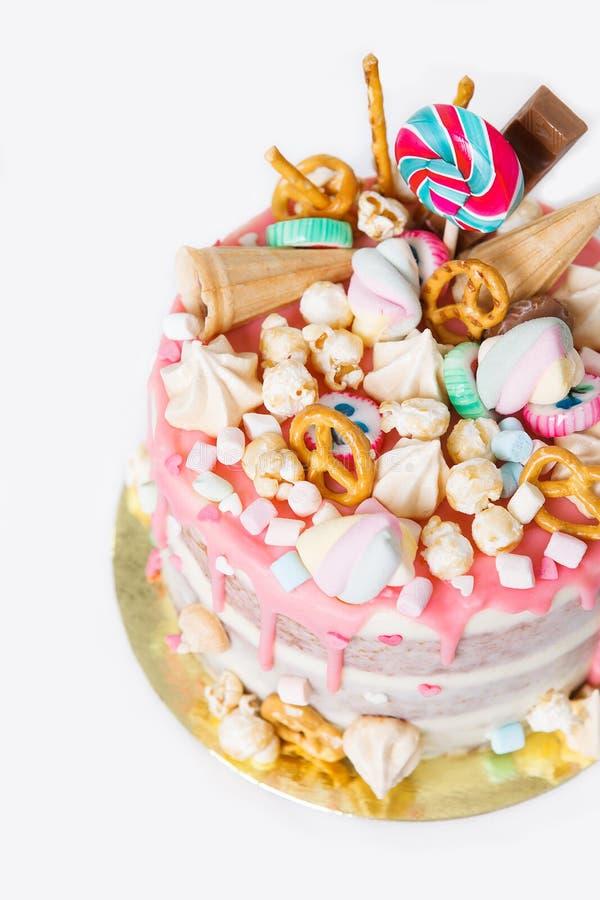 Torta di compleanno con decorato con le caramelle, lecca-lecca, caramelle gommosa e molle Colore pastello rosa Palloni su fondo P fotografie stock libere da diritti