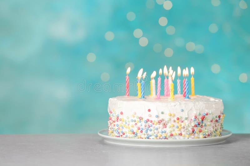 Torta di compleanno con le candele brucianti sulla tavola contro fondo blu-chiaro fotografia stock libera da diritti