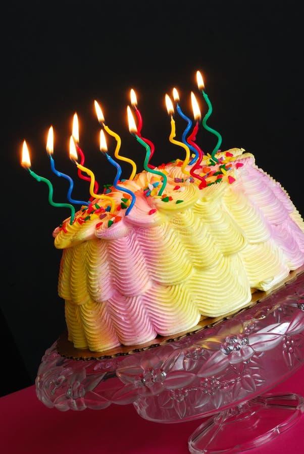 Torta di compleanno con le candele illuminate fotografia stock libera da diritti
