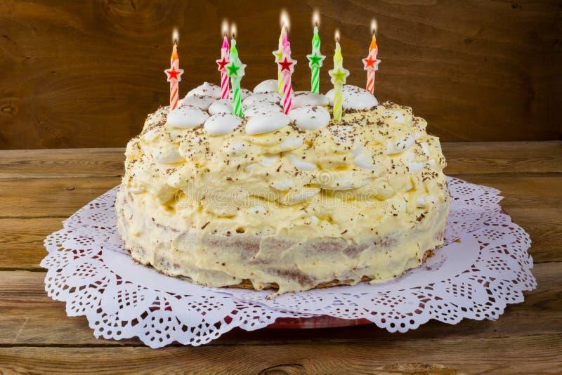 Torta di compleanno con le candele su fondo di legno fotografia stock libera da diritti