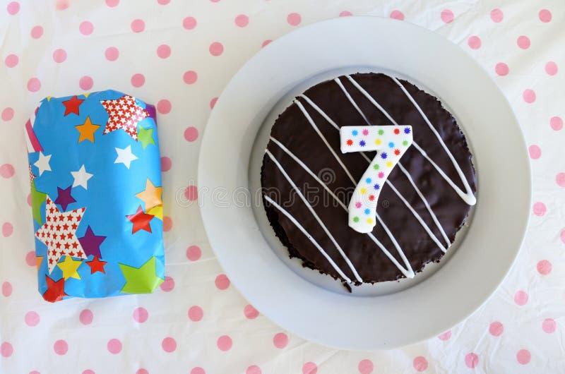 Torta di compleanno del cioccolato e del presente per un settimo compleanno o immagini stock