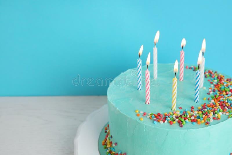 Torta di compleanno deliziosa fresca con le candele sulla tavola contro il fondo di colore fotografie stock