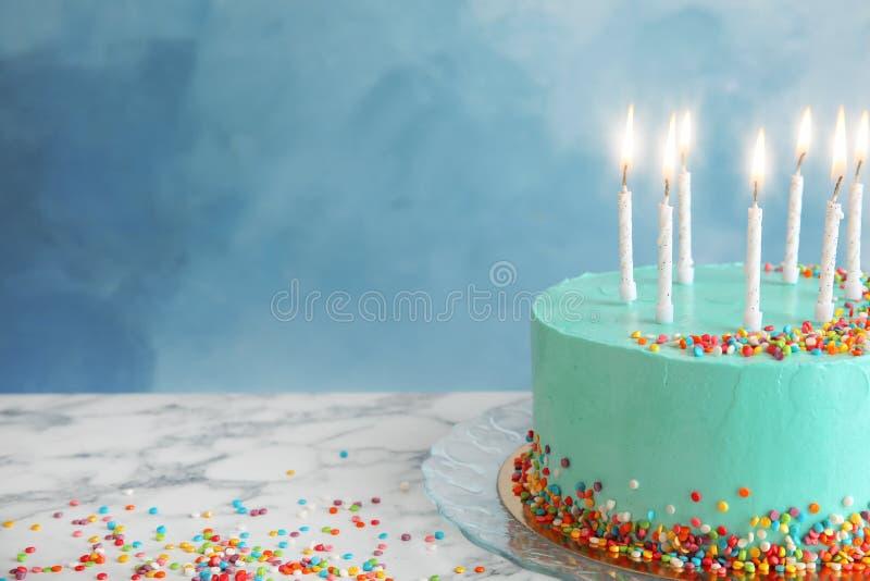 Torta di compleanno deliziosa fresca con le candele sulla tavola contro il fondo di colore fotografia stock libera da diritti