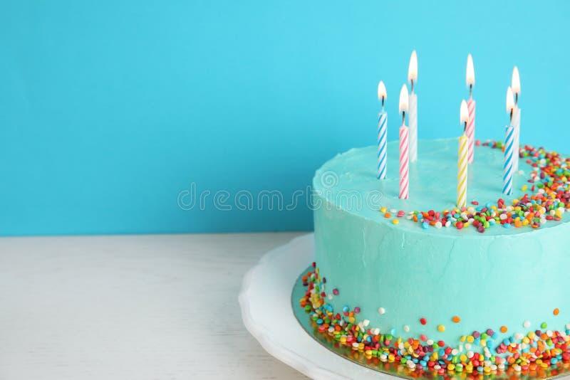 Torta di compleanno deliziosa fresca con le candele sulla tavola contro il fondo di colore immagine stock