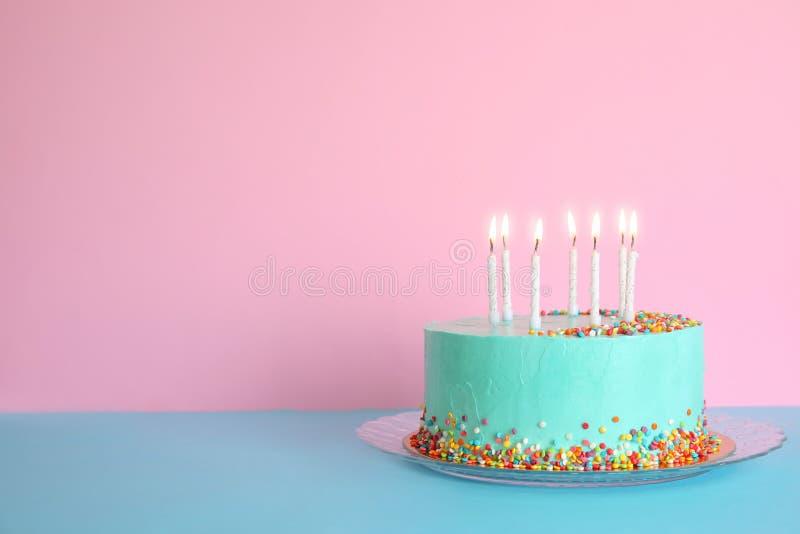 Torta di compleanno deliziosa fresca con le candele sulla tavola contro il fondo di colore fotografia stock