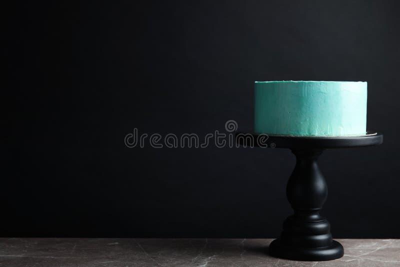 Torta di compleanno deliziosa fresca sul supporto contro fondo nero fotografia stock