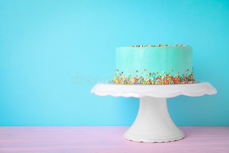 Torta di compleanno deliziosa fresca sul supporto contro il fondo di colore immagini stock libere da diritti