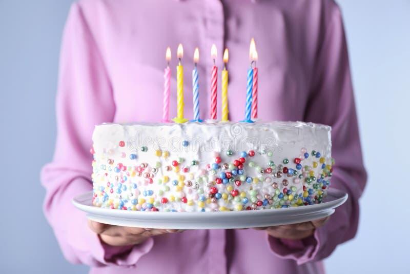 Torta di compleanno della tenuta della donna con le candele brucianti, immagine stock libera da diritti