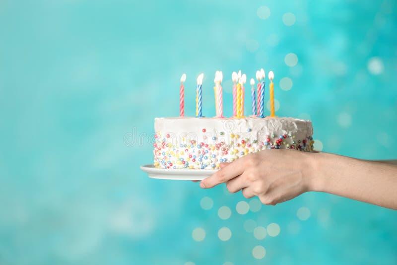 Torta di compleanno della tenuta della donna con le candele brucianti su fondo blu-chiaro, immagine stock libera da diritti