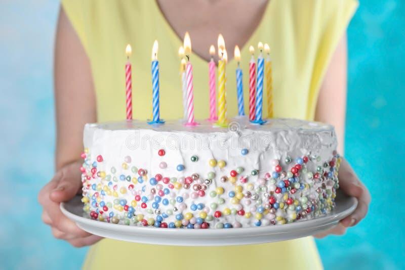 Torta di compleanno della tenuta della donna con le candele brucianti su fondo blu-chiaro, fotografia stock libera da diritti