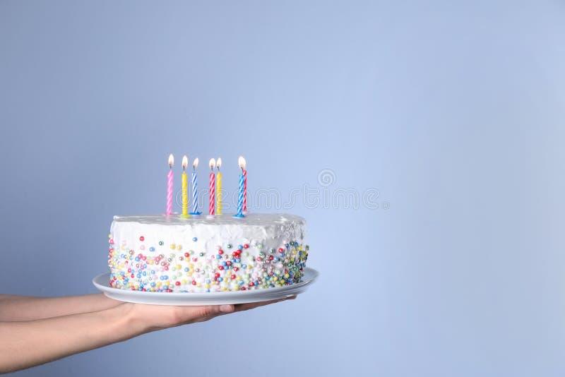 Torta di compleanno della tenuta della donna con le candele brucianti su fondo blu-chiaro, primo piano fotografie stock libere da diritti