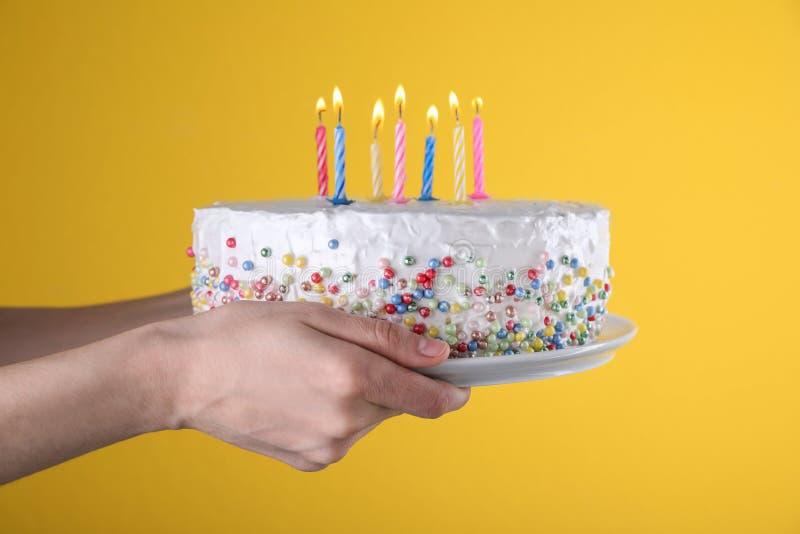 Torta di compleanno della tenuta della donna con le candele brucianti su fondo giallo, fotografie stock libere da diritti